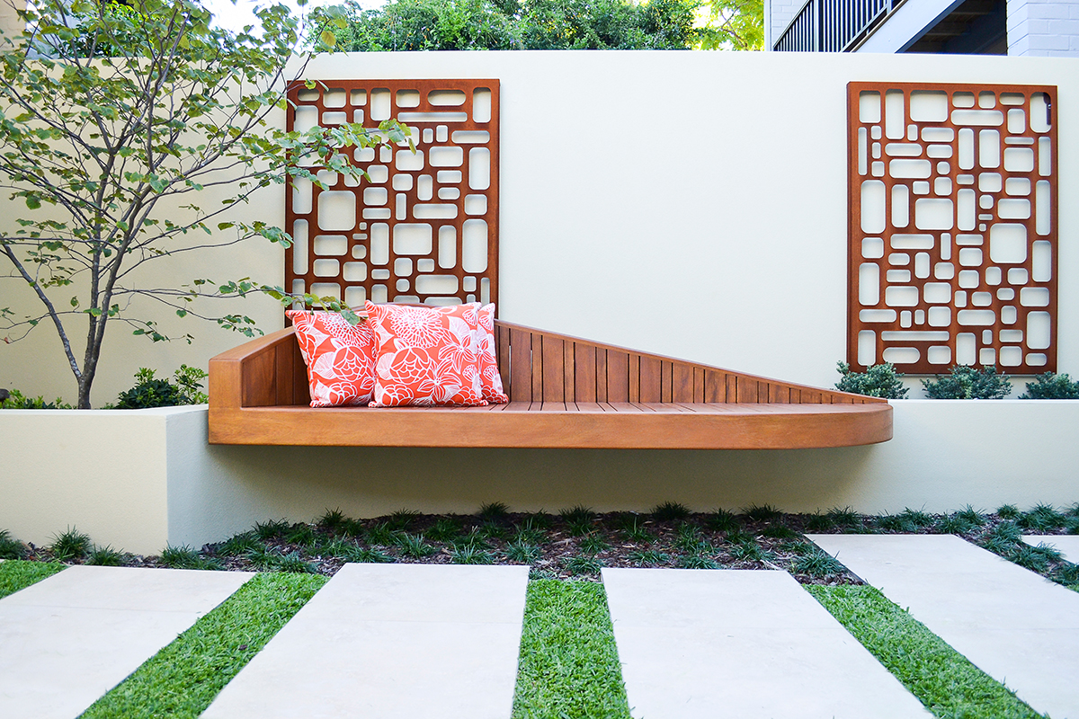 A photo of the courtyard garden with floating wood bench seat