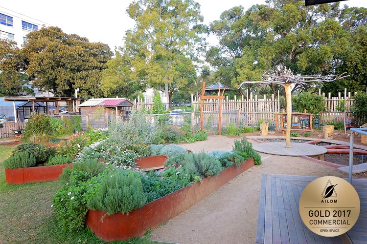 Raised corten planter boxes with lush planting, and featured recycled timber tree