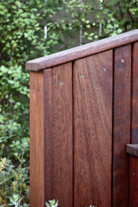 Bespoke timber seat with backrest nestled into the garden