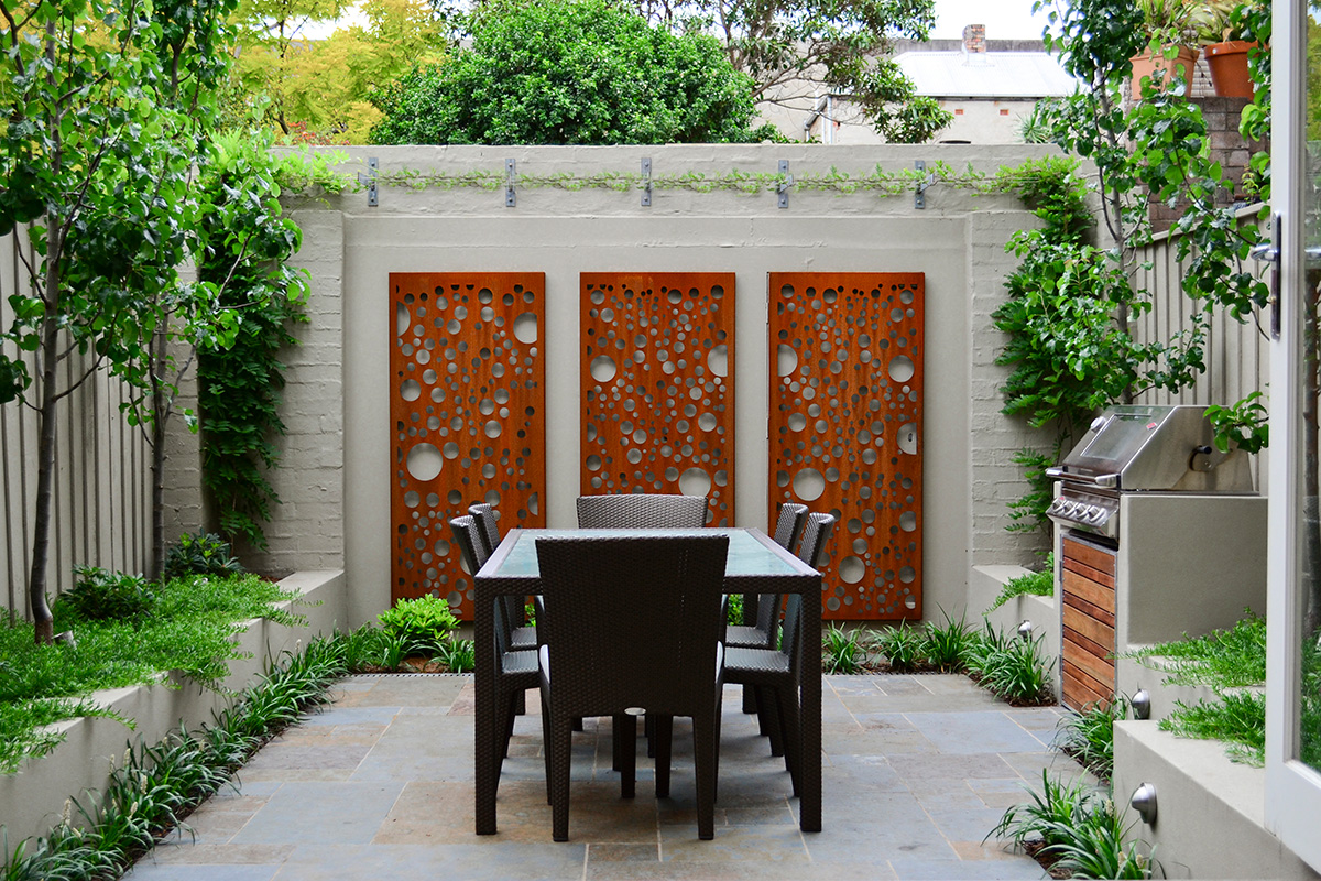 An outdoor table surrounded by raised gardens and feature screens
