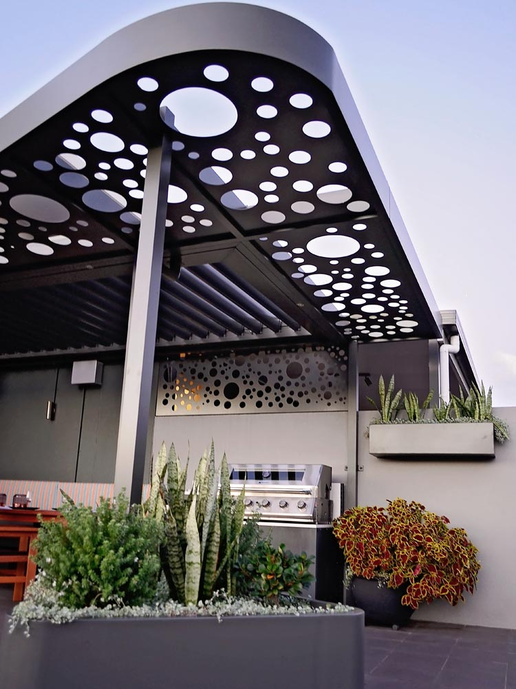 Low angle image of feature powder coated pergola over BBQ area