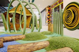 Crawl tunnel and artificial turf mounds create an adventurous playground for toddlers