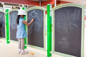 A girl playing on the interactive chalkboards