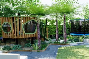 Bespoke timber tree house with viewing windows and slide among shady tree ferns and trampoline play