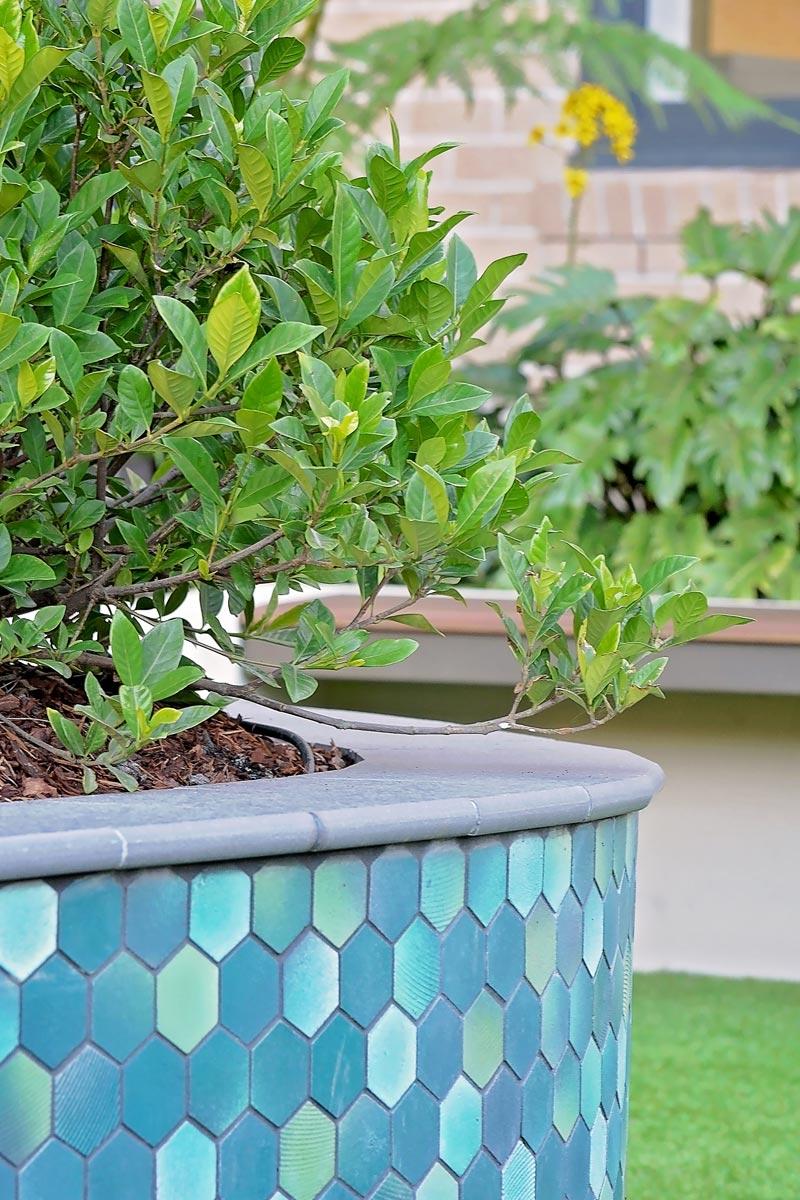 Closeup of raised planter with hexagonal tile cladding